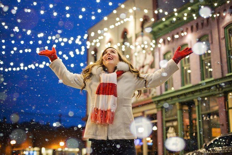 Frau freut sich über Lichter und Schnee zu Weihnachten.
